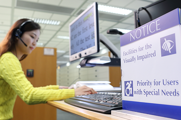 A student using a screen magnifier at the designated station with priority for users with special needs