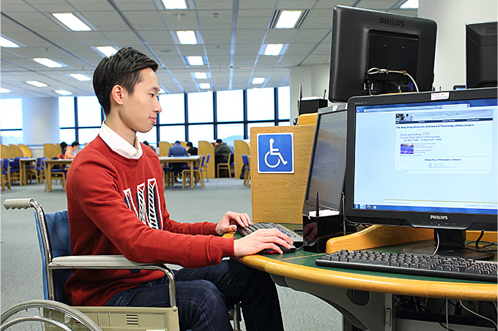 A wheelchair user looking up information in the Library