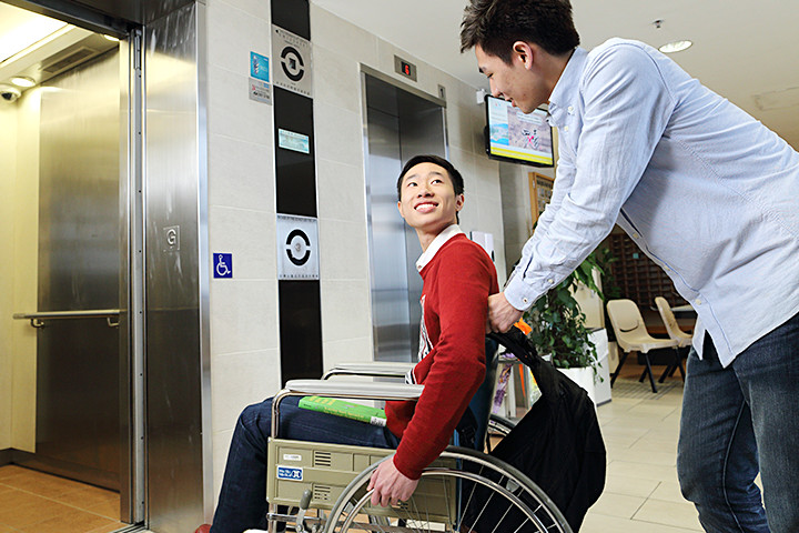 A student helping a wheelchair user to enter an elevator in student hall