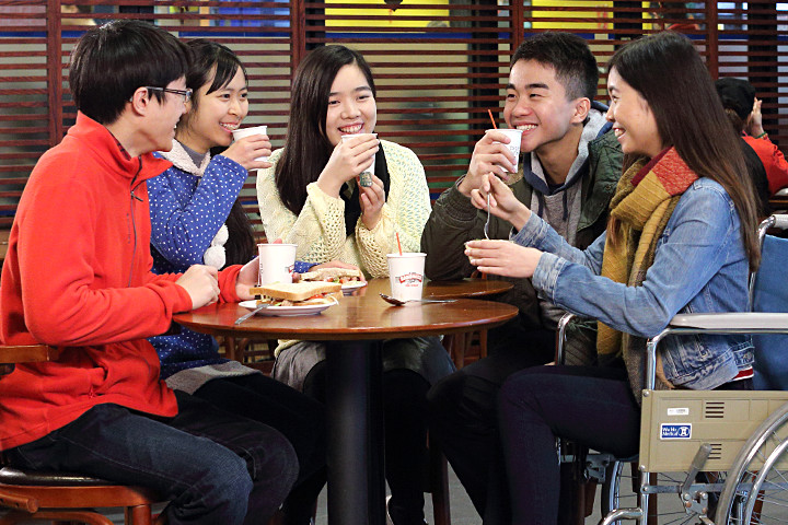 5 students chatting at Coffee Shop, including a wheelchair user